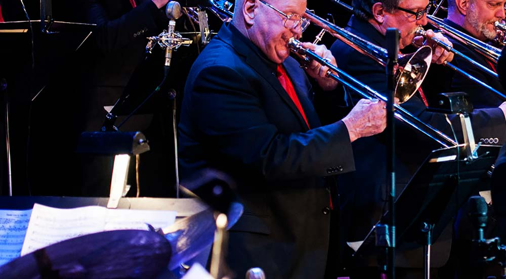 A trombonist playing a solo during a swing era jazz standard.
